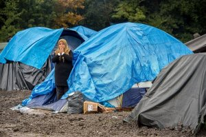 A woman stands at the entrance of a tent, on October 20, 2015 in a makeshift camp in Grande-Synthe, where 500 to 700 people - most seeking to get to England - have set up camp.  AFP PHOTO PHILIPPE HUGUEN        (Photo credit should read PHILIPPE HUGUEN/AFP/Getty Images)