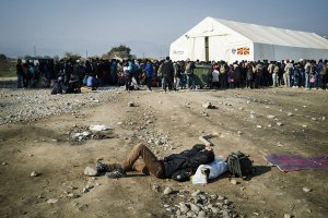 A man rests as he waits along with other migrants and refugees at a registration camp after crossing the Greece-Macedonia border near Gevgelija on November 14, 2015. Several EU countries have reintroduced border checks as Europe struggles under the strain of its worst migrant crisis since World War II, threatening to undermine the bloc's cherished passport-free Schengen zone.   AFP PHOTO / DIMITAR DILKOFF        (Photo credit should read DIMITAR DILKOFF/AFP/Getty Images)