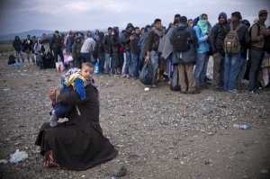 A Syrian woman changes her child's diaper as migrants and refugees queue at a camp to register after crossing the Greek-Macedonian border near Gevgelija on September 22, 2015. EU interior ministers were set to hold emergency talks to try and bridge deep divisions over Europe's worst migrant crisis since World War II, as pressure piles onto member states to reach an agreement. AFP PHOTO / NIKOLAY DOYCHINOV        (Photo credit should read NIKOLAY DOYCHINOV/AFP/Getty Images)
